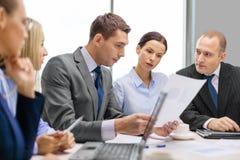 Équipe d'affaires avec l'ordinateur portable ayant la discussion Photo stock
