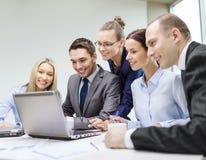 Équipe d'affaires avec l'ordinateur portable ayant la discussion Photographie stock