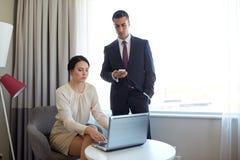 Équipe d'affaires avec l'ordinateur portable fonctionnant à la chambre d'hôtel Image stock