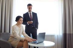 Équipe d'affaires avec l'ordinateur portable fonctionnant à la chambre d'hôtel Images stock