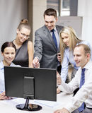 Équipe d'affaires avec le moniteur ayant la discussion Image stock