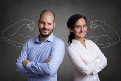 Équipe d'affaires avec les bras musculaires se tenant devant un bla gris photographie stock libre de droits
