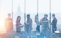 Équipe d'affaires dans le bureau, paysage urbain de matin Images stock