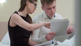 Équipe d'affaires de deux fonctionnant avec des documents, discutant des bilans financiers et analysant des statistiques Photos libres de droits