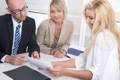Équipe d'affaires de l'homme une femme s'asseyant autour d'un pouvoir adiathermique parlant de table Images stock