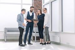 Équipe d'affaires discutant de nouvelles idées, se tenant dans le lobby de bureau image stock