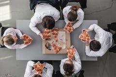 Équipe d'affaires mangeant de la pizza images stock