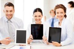 Équipe d'affaires montrant des PCs de comprimé dans le bureau Image stock