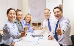 Équipe d'affaires montrant des pouces dans le bureau Photo stock