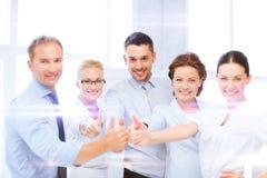 Équipe d'affaires montrant des pouces dans le bureau Photographie stock