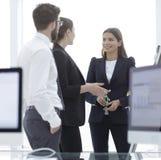 Équipe d'affaires parlant le bureau proche debout Images stock