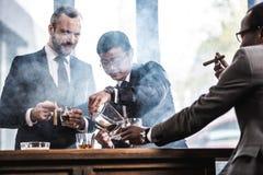 Équipe d'affaires passant le temps, cigares de tabagisme et buvant du whiskey Image stock