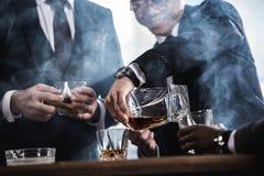 Équipe d'affaires passant le temps, cigares de tabagisme et buvant du whiskey Photos libres de droits