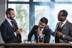 Équipe d'affaires passant le temps, cigares de tabagisme et buvant du whiskey Images stock