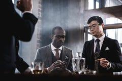 Équipe d'affaires passant le temps, cigares de tabagisme et buvant du whiskey Images libres de droits