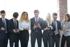 Équipe d'affaires regardant au smartphone dans le bureau Image libre de droits