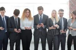 Équipe d'affaires regardant au smartphone dans le bureau Photographie stock