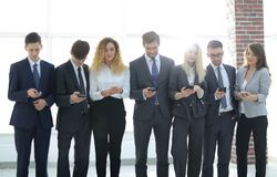 Équipe d'affaires regardant au smartphone dans le bureau Photographie stock libre de droits