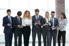 Équipe d'affaires regardant au smartphone dans le bureau Image stock