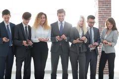 Équipe d'affaires regardant au smartphone dans le bureau Photo libre de droits