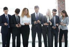 Équipe d'affaires regardant au smartphone dans le bureau Images stock