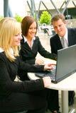 Équipe d'affaires regardant l'ordinateur portatif Image stock