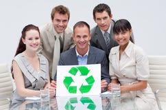 Équipe d'affaires retenant un symbole de réutilisation Images libres de droits