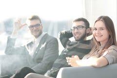 Équipe d'affaires s'asseyant sur le divan pendant la pause photos stock