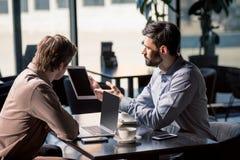 Équipe d'affaires sur la réunion discutant le projet avec le comprimé numérique en café Photos libres de droits