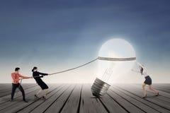 Équipe d'affaires tirant la lampe extérieure Photographie stock libre de droits