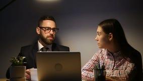 Équipe d'affaires travaillant des heures supplémentaires en retard sur l'ordinateur portable sur le lieu de travail confortable clips vidéos