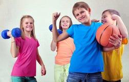 Équipe d'amis folâtres d'enfants avec les haltères et la boule Image libre de droits