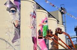 Équipe d'artistes peignant des peintures murales sur des silos dans la zone idustrial images stock