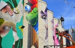 Équipe d'artistes peignant des peintures murales sur des silos dans la zone idustrial photographie stock