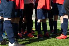 Équipe d'enfants du football sur le champ vert image stock