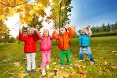 Équipe d'enfants jouant avec des feuilles de vol Photo libre de droits