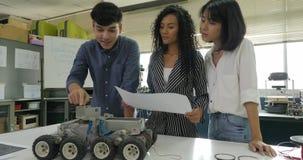 Équipe d'ingénieur électronicien travaillant ensemble, collaborant sur un projet pour construire le robot clips vidéos