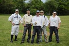 Équipe de baseball dans l'uniforme du 19ème siècle de vintage pendant le jeu de boule de base de style ancien après les règles et Image libre de droits