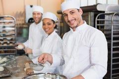 Équipe de boulangers souriant à l'appareil-photo images libres de droits