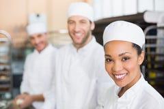 Équipe de boulangers souriant à l'appareil-photo image stock