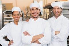 Équipe de boulangers souriant à l'appareil-photo Image libre de droits