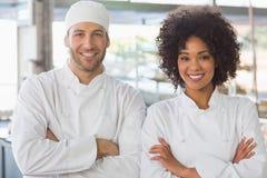 Équipe de boulangers souriant à l'appareil-photo Photos stock