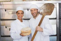 Équipe de boulangers souriant à l'appareil-photo avec le pain Photographie stock