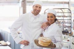 Équipe de boulangers souriant à l'appareil-photo avec le pain images stock