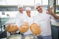 Équipe de boulangers souriant à l'appareil-photo tenant le pain photos stock