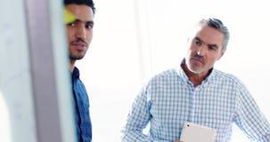 Équipe de cadres commerciaux discutant au-dessus du conseil de verre banque de vidéos