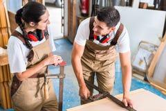 Équipe de charpentiers comparant des morceaux de travail Photo stock