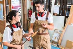 Équipe de charpentiers comparant des morceaux de travail image stock