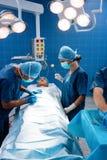 Équipe de chirurgie actionnant un patient dans une salle d'opération image libre de droits