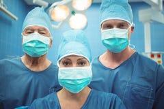 Équipe de chirurgiens portant le théâtre en fonction de masque chirurgical Images libres de droits